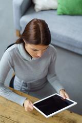 frau sitzt zuhause am tisch und liest an ihrem tablet