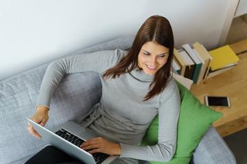 entspannte frau mit ihrem notebook auf der couch