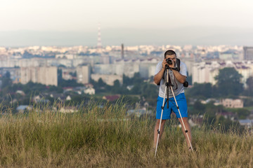 Photographer with a camera on a tripod taking picture with blurr