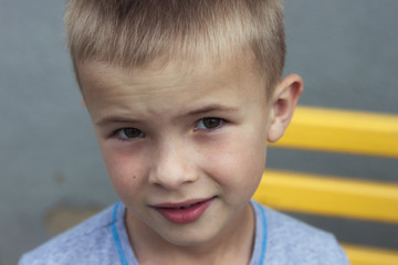 Portrait of a little smiling boy with golden blonde straw hair i