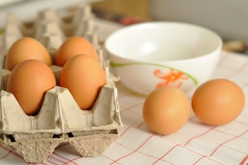 Raw eggs in box and plate