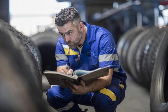 Man in tire repair factory taking notes