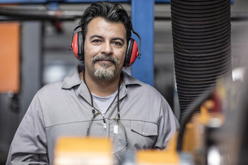 Portrait of smiling man with earmuffs in factory