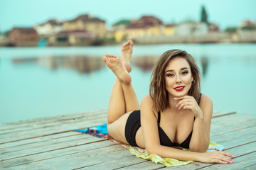 Portrait of gorgeous dark-haired smiling girl with red lips in black swimming suit lying on the wooden pier at the lake.  Resort and spa concept. Outdoor shot. Copy-space