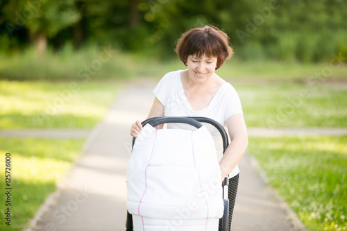 6e68c8e76ddb Portrait of happy middle-aged mother walking in park on summer sunny ...