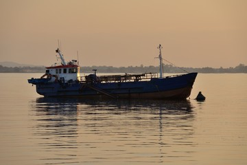 fishing boat anchored at sunset