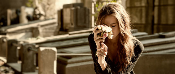 Sad woman holding bunch of flowers near a grave letterbox
