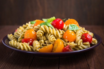 Fusilli pasta salad with pesto genovese, colorful tomatoes and basil leaves on dark wooden background close up. Italian cuisine. Delicious meal.
