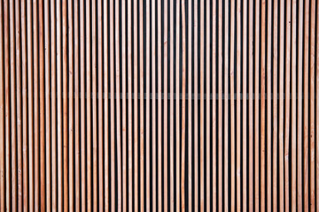 Various tone of wooden stripes use as wall partition or fence cladding in vertical line which also...