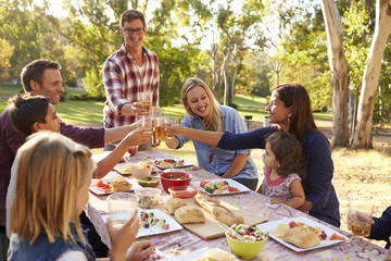 Two families making a toast at picnic at a table in a park Wall mural