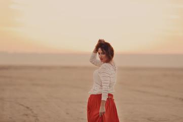 Молодая красивая девушка в белой кофте идет по пустыне на закате