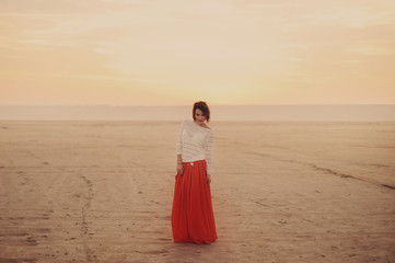 Молодая красивая девушка в белой кофте и длинной оранжевой юбке стоит в пустыне на закате