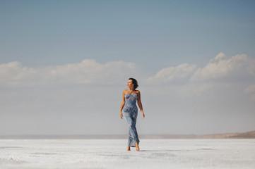 Молодая стройная женщина идет по  пустыне в длинном узком платье