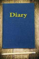 Diary with pencil on wood