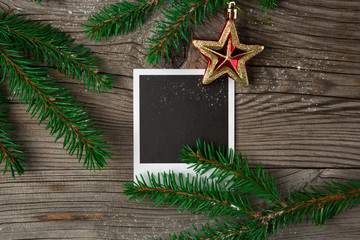 Christmas wooden background with photo frame, red star and snow fir tree. Top view with copy space. Holiday concept