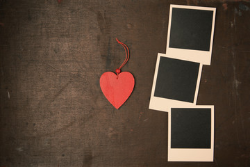 Retro Vintage empty Photo frames and red wooden heart on old dark Background. Top view with copy space. Toned
