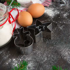 Christmas background with cookies cutters, flour, spices, eggs and snow fir tree on old rustic wooden table, selective focus with copy space.