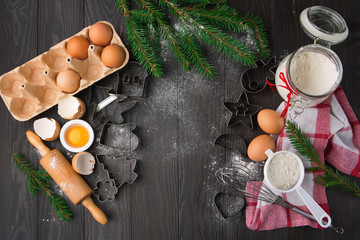 Christmas background with cookies cutters, flour, spices, eggs and snow fir tree on old rustic wooden table, top view with copy space. Holiday concept