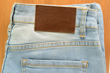 empty brown leather tag on white jeans