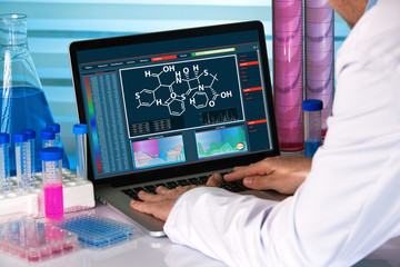 research scientist using computer chemistry lab / chemical engineer working with analysis software on laptop in the research laboratory