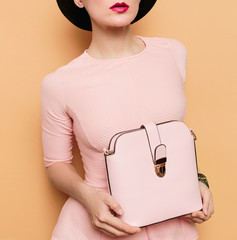 Girl in retro style. Accessories hat and bag. Vanilla style fash