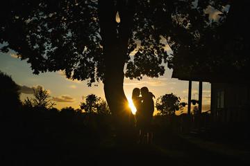 Cuddling couple on sunset background
