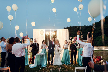 Newlyweds and their friends pull balloons in the air after the c Fototapete