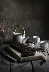 Tea time: teapot, cups of tea and dark chocolate on wooden table