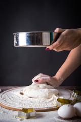 Spread the flour through a sieve on the dough. On a black background.