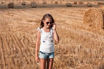 Beautiful girl at sunset in haystacks. Girl with long hair in haystacks.