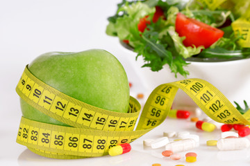 Diet concept - green apple, tablet, tape measure and lettuce