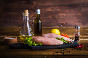 Cooking chicken. The table with the ingredients for the dishes. On a wooden background.