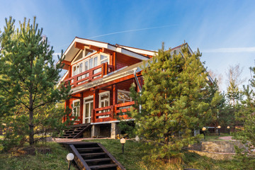 Beautiful red log cabin with porch at sunset
