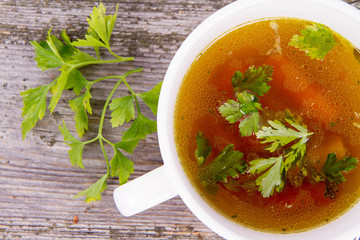 Chicken soup with carrots and parsley on wooden background