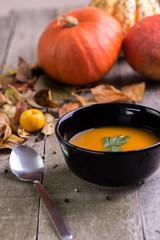 Autumn pumpkin soup on natural wooden table.