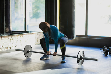 Muscular woman in a gym doing deadlift