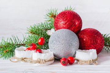 Новогодний натюрморт - елочные шары, чайные свечи, ягоды шиповника и еловые ветки на деревянном фоне