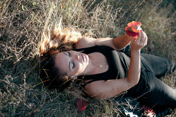 Girl with leaves lying on the grass