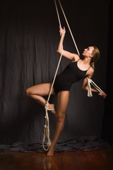 Beautiful gymnast hanging on a rope