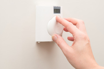 Hand Adjusting Dial on Wall Mounted Thermostat