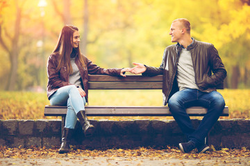 Young couple is sitting on a bench in a park on a beautiful Autumn day. They are talking to each other, and holding hands