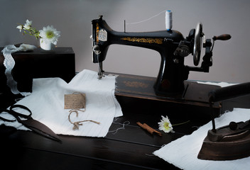 Classic retro style manual sewing machine ready for  work. The  is old  made of metal with floral patterns