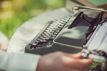 Young man writing a letter on old typewriter