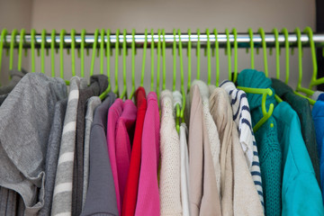 Women's clothing hanging on hangers. Colored jackets and sweater