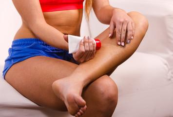 Woman applying cream taking care of her skin
