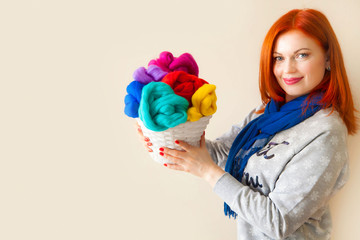 A woman holding a basket of white skeins of wool for felting. ca