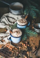 Hot chocolate in blue mugs with whipped cream and cinnamon sticks, spices, nuts, cocoa powder and fir-tree branches on rustic wooden background, selective focus, vertical composition