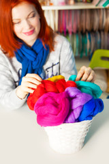 A woman holding a basket of white skeins of wool for felting.