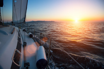 Wall Mural - Yacht sailing against sunset. Luxury boat. Vacation and Travel Concept.