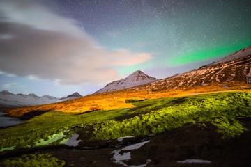 The Aurora Borealis over the mountains range of Stodvarfjordur town in East Iceland.